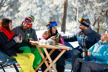 Friends spending time together and drink after skiing in cafe at ski resort