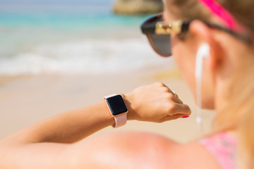 Woman looking at smartwatch on the beach