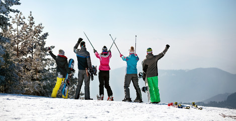 Back view of Happy skiing group on the mountain top.