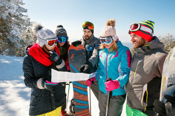 friends reading a paper map in winter holidays in snowy mountain