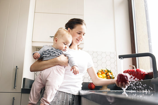 Mother with baby in kitchen. Healthy food concept