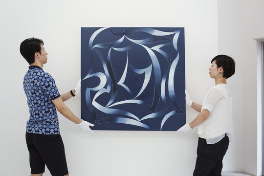 Man in blue shirt and woman wearing white shirt hanging modern painting on white wall in art gallery.