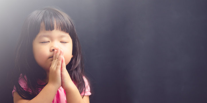 Little girl praying in the morning.Little asian girl hand praying,Hands folded in prayer concept for faith,spirituality and religion.Black background.