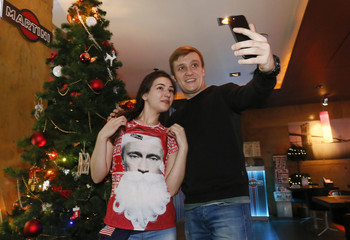 A visitor takes a selfie with a waiter of a coffee bar who wears a T-shirt with an image of Russian President Putin dressed as Santa Claus in Krasnoyarsk