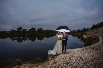 Couple newlyweds with big umbrella