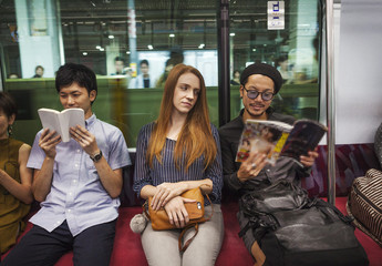 Three people sitting sidy by side on a subway train, reading,Tokyo commuters.