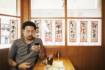 Man seated at small table in a cafe, looking at his smartphone.