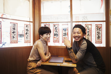 Two people, smiling man and woman seated at small table in a cafe.