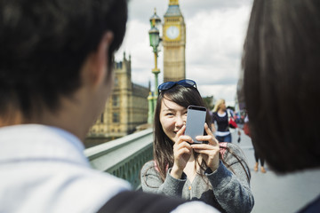 Smiling woman with black hair taking picture of couple with smartphone, standing on Westminster Bridge over the River Thames, London, with the Houses of Parliament and Big Ben in the background.
