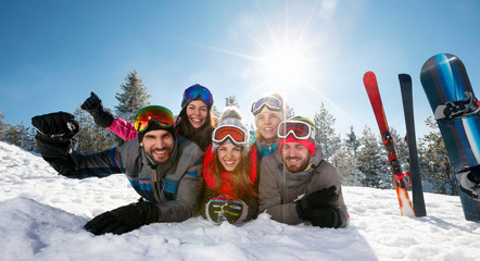 Smiling friends having fun on ski holiday in mountains