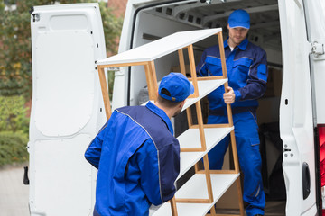 Two Delivery Men Unloading Shelf From Truck