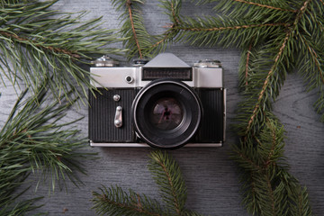 retro camera and christmas fir tree branches, decorations wooden background. flat lay. top view