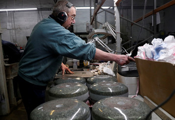 Kays Factory worker John Brown polishes granite by hand to make a curling stone in Mauchline, Scotland