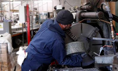 Kays Factory worker Allan Walsh puts granite on the lathe to make a curling stone in Mauchline, Scotland