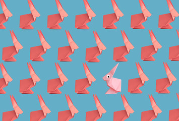 Origami red and pink bunnies pattern on a blue background