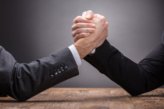Two Businesspeople Competing In Arm Wrestling