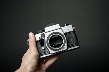 man's hand holding a old camera on a black background