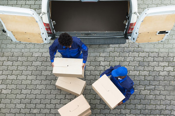 Delivery Men Unloading The Cardboard Boxes