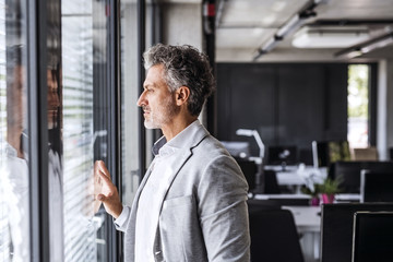 Mature businessman in office loooking out of window