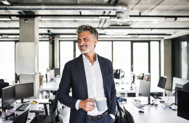 Smiling mature businessman with coffee mug in office