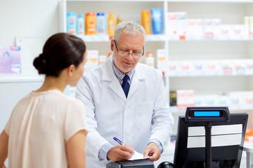 senior apothecary with prescription at pharmacy