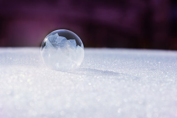 close up of frozen bubble on winter snow during freezing day