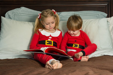 adorable brother and sister siblings reading storytime while wearing christmas pajamas