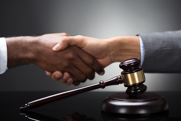 Mallet And Gavel In Front Of Two Businesspeople Shaking Hands