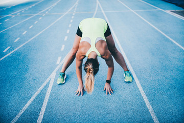 Young female athlete stretching on running track