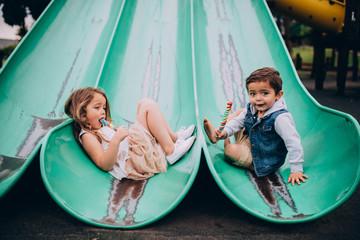 Siblings sitting on slide on playground