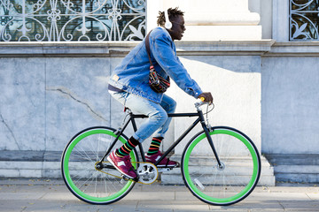 Handsome young man riding bike in the street.