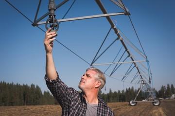 Farmer checking irrigation system in field