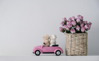 Love concept of couple teddy bear on pink toy car and paper roses in basket minimal style