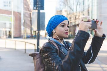 Arabian young woman wearing hijab using smart phone listening music