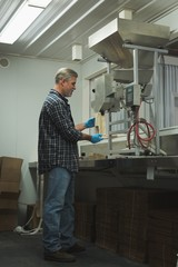 Man refining grain in machine