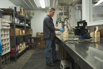 Man packing grains with machine
