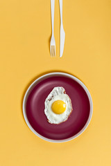 Fried egg on a burgundy plate on a yellow background. Breakfast in a minimalist style..
