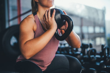 Woman doing workout with kettlebell in gym