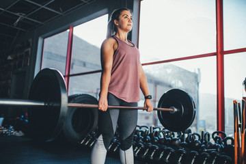 Fit young adult woman exercising with barbell in gym