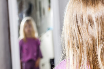 Little girl dancing and standing in front of the mirror