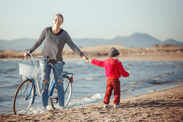 attractive young sport woman on the spring desert sea beach by bike with baby