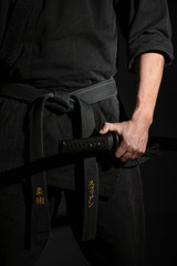 Black judo, aikido, or karate belt, tied in a knot with a hand holding a japanese sword called laïto on black background