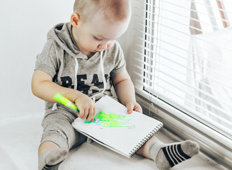 Happy little boy is playing with colorful markers, sitting on windowsill