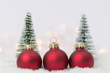 drei rote Christbaumkugeln im Schnee mit Tannenbäumen