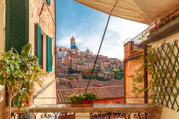 Papiers peints Toscane Beautiful view of Dome and campanile of Siena Cathedral, Duomo di Siena, and Old Town of medieval city of Siena in the sunny day through autumn leaves, Tuscany, Italy