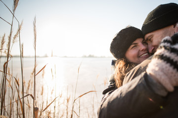 Smiling couple hugging in winter forest