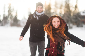 Cheerful girlfriend holding her man's hand while running