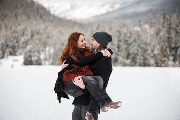 Young man wearing beanie cap holding his girlfriend in arms
