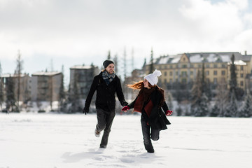 Young joyful couple enjoying the winter season