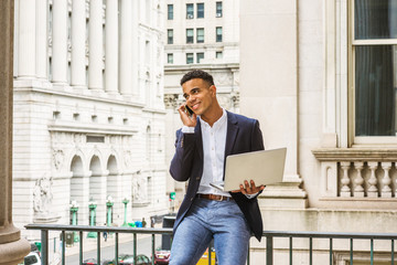 African American Businessman works in New York. Wearing black blazer, white shirt, young man sits on street by vintage office building, works on laptop computer, talks on cell phone. Filtered effect..